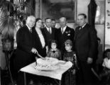 Adults posing with children and cutting a cake, publicity photo
