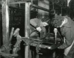 Two women operate machinery at the Budd Company