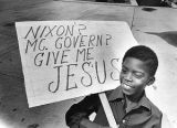 Boy holds sign during march for Christ