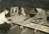 Workers look at ship template