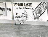Two baseball players in front of advertisement.