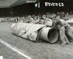 Groundskeepers roll out a tarp at Connie Mack Stadium