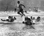 Baseball fans splash in the rain on infield tarp at Veterans Stadium