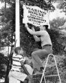 Sailor fixes sign while children watch
