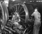 Wheel turning process completed by worker in Baldwin Locomotive Works