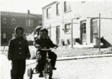 Boys play on tricycle at Richard Allen Homes