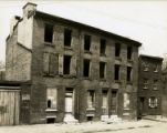 Exteriors of three dilapidated houses on Water Street 19147